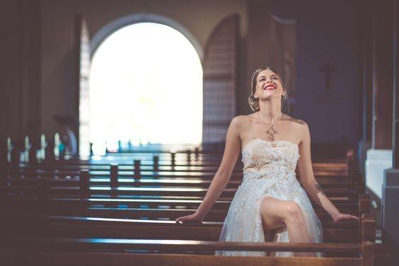 Photo d'une mariée, souriante, assise dans une église.